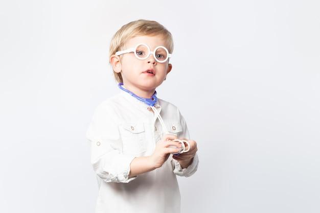Médico criança engraçada com óculos e estetoscópio no fundo branco com espaço de cópia