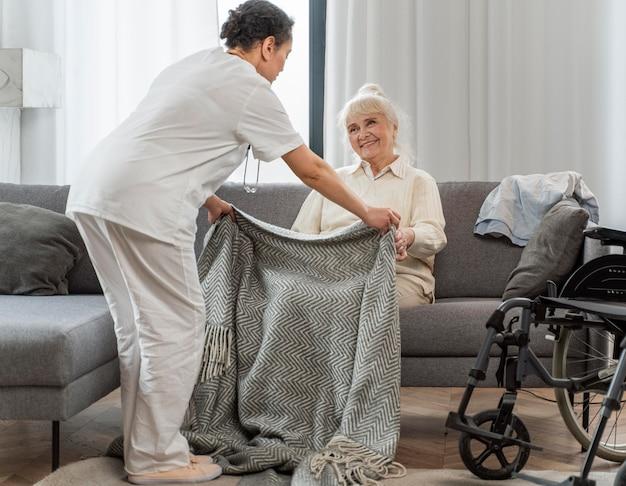 Médico cuidando de mulher idosa em casa