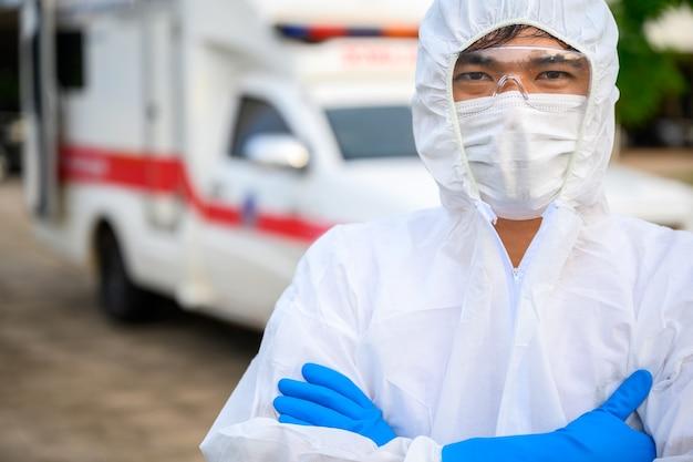 Médico da linha de frente parado em uma ambulância de emergência use um uniforme de epi e uma ambulância carregando o corpo dos mortos por doença coronavírus covid19