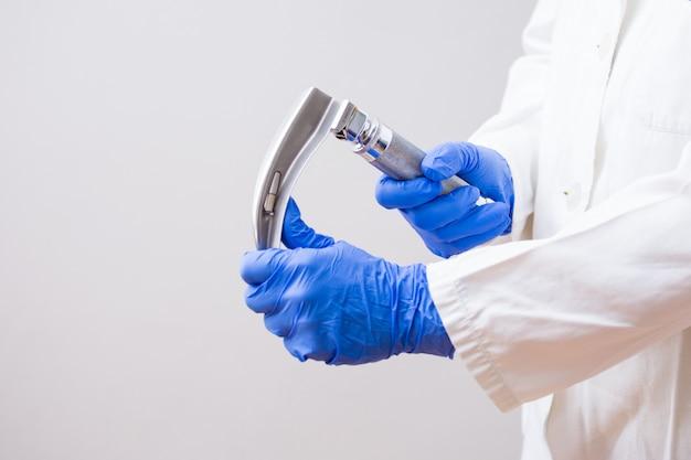 Médico da mão segurando o laringoscópio