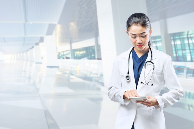 Médico da mulher asiática no jaleco branco e estetoscópio usando tablet
