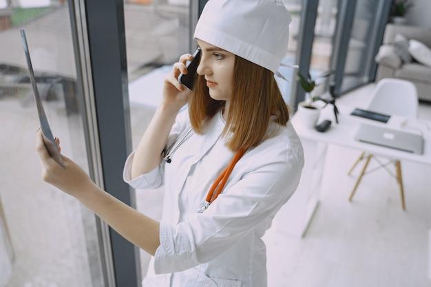 Médico da mulher com jaleco branco no hospital