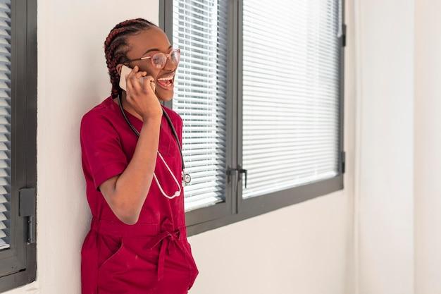 Médico da mulher dando um tempo e falando em seu telefone