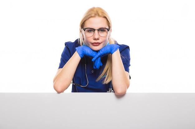 Médico da mulher de bata azul e luvas com máscara facial
