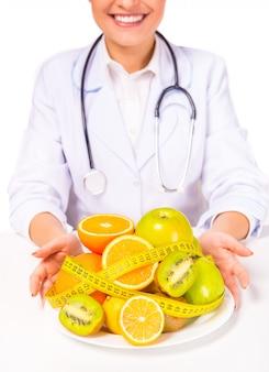 Médico da mulher em um jaleco branco com frutas.