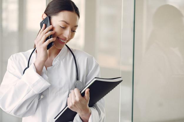 Médico da mulher em um uniforme branco em pé em um corredor
