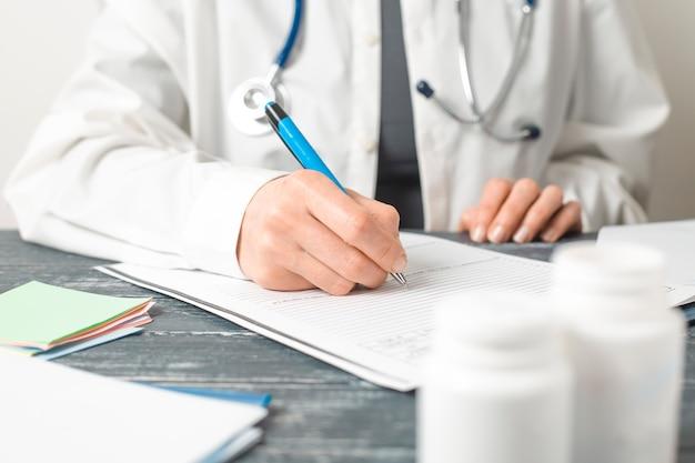 Médico da mulher escreve um relatório médico no escritório da clínica.