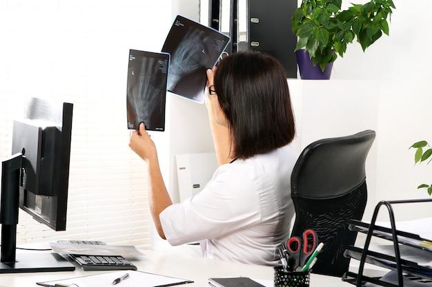 Médico da mulher está olhando o raio x da mão quebrada