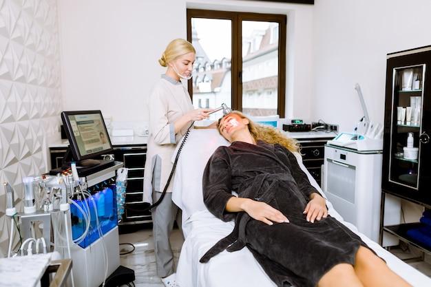 Médico da mulher fazendo terapia de luz led vermelha para jovem na clínica de beleza, terapia de foto facial para a pele.