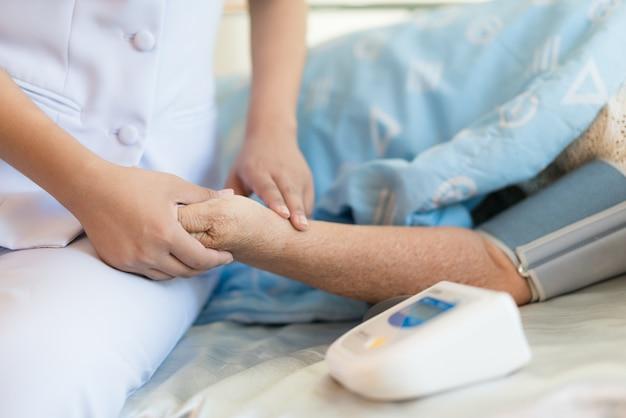 Médico da mulher medido no sangue do paciente idoso no quarto de hospital.