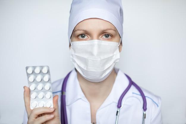 Médico da mulher segurando comprimidos brancos em close-up de mãos.
