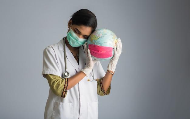Médico da mulher segurando o globo do mundo com uma máscara de medicina. epidemia mundial do conceito de coronavírus.