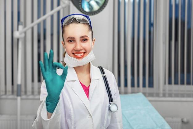 Médico da mulher tirando a máscara sorri para a câmera e coloca a mão bem no contexto de uma enfermaria do hospital.
