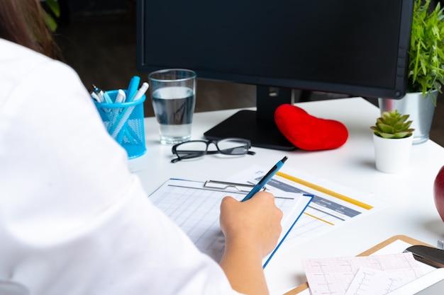 Médico da mulher tomando notas na área de transferência enquanto está sentado em sua mesa no escritório