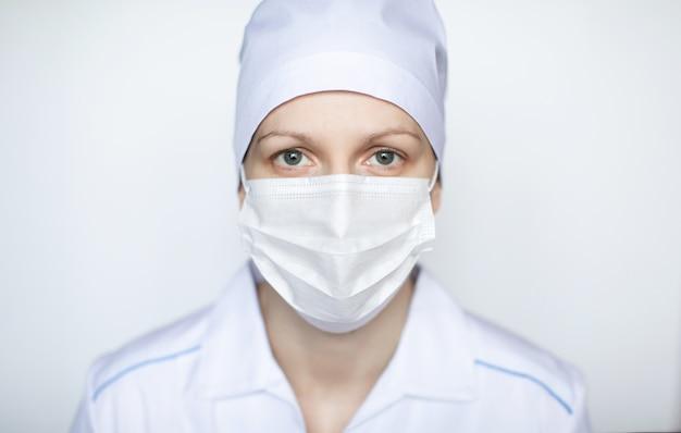 Médico da mulher usando máscara protectiv em fundo branco.