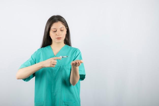 Médico da mulher vestindo uniforme verde, segurando a seringa em branco.