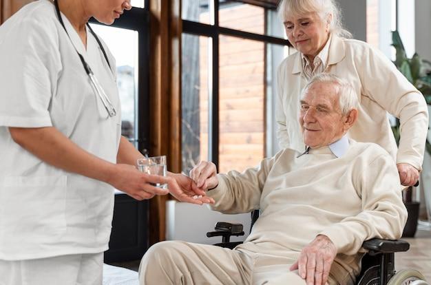 Médico dando comprimidos para seu paciente