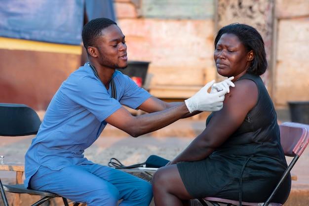 Médico de ajuda humanitária da áfrica cuidando de paciente