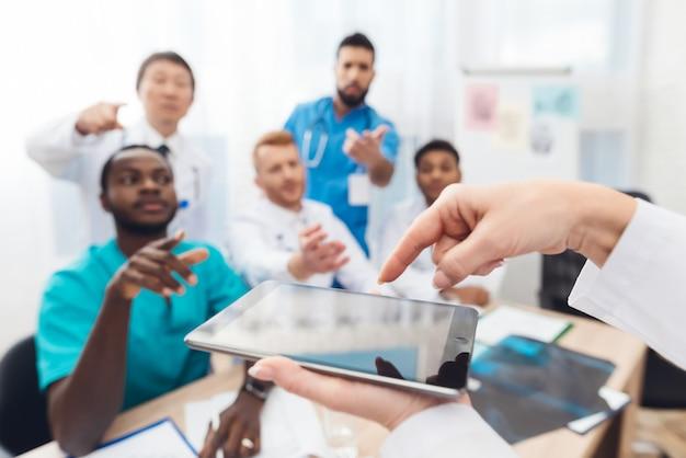 Médico de cabeça feminina mostra colegas algo sobre o tablet.