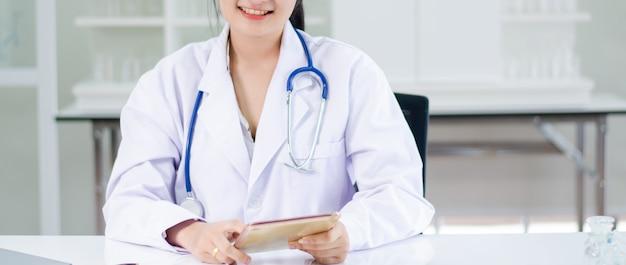 Médico de cabelo comprido de mulheres segurando o tablet