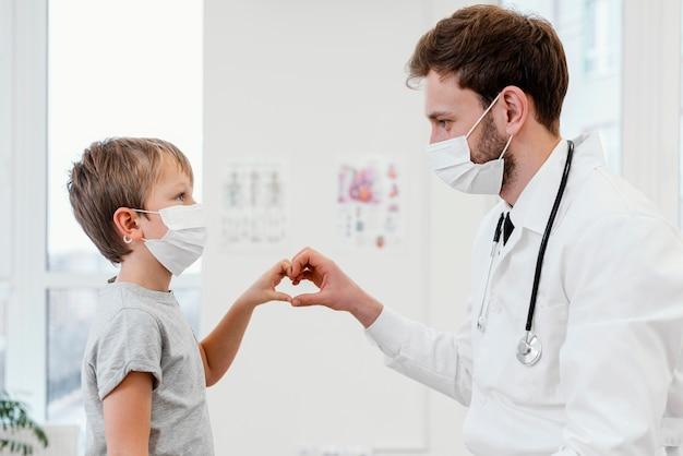 Médico de close-up e criança usando máscaras
