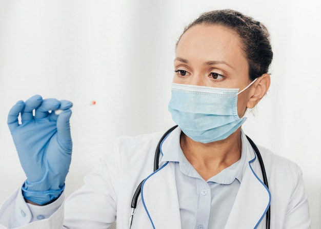 Médico de close-up segurando um cotonete