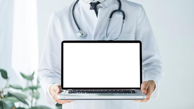 Médico de colheita mostrando laptop com tela vazia