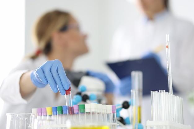 Médico de diagnóstico de laboratório segurando tubo de ensaio de vidro em luva de borracha