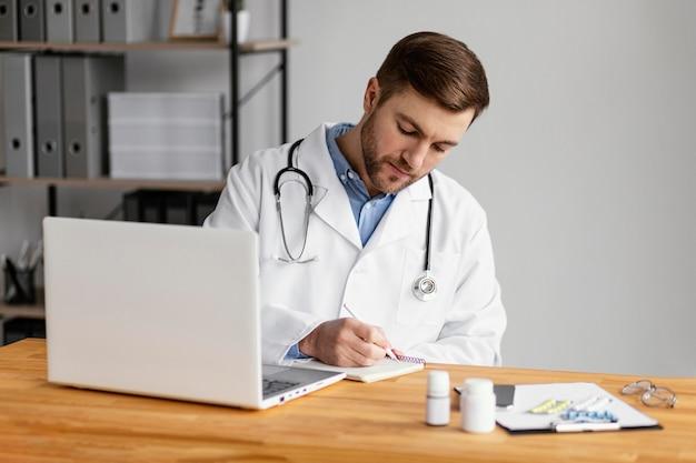 Médico de dose média redigindo receita