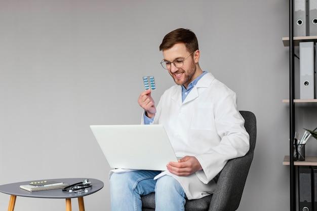Médico de dose média segurando bolha de comprimido