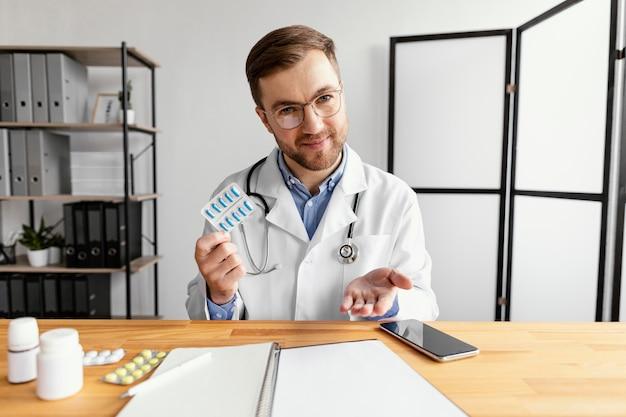 Médico de dose média segurando comprimidos
