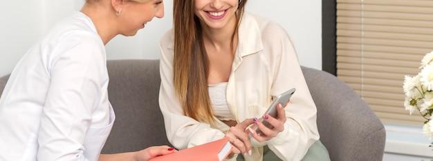 Médico de duas jovens com paciente sorrindo e olhando para o smartphone sentado no escritório do hospital, consulta com um médico.
