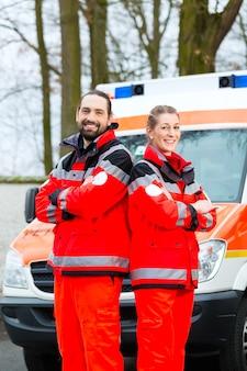 Médico de emergência e enfermeira em frente ao carro da ambulância