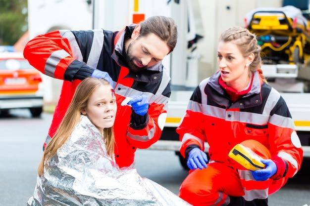 Médico de emergência e equipe de paramédico ou ambulância ajudando vítima de acidente