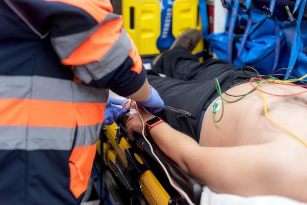 Médico de emergência, verificando o pulso de um paciente na ambulância