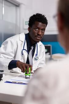 Médico de etnia afro-americana segurando carimbo