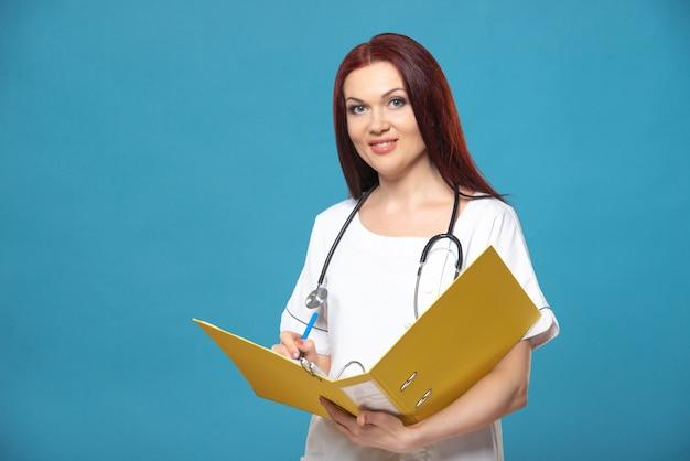 Médico de família mulher feminina com um estetoscópio mantém pasta com documentos