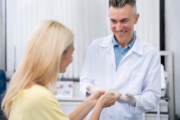 Médico de injeção média e mulher com implantes mamários