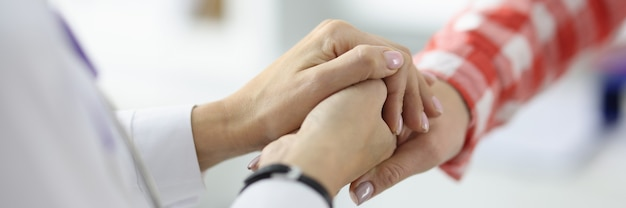 Médico de jaleco branco apertando as mãos de paciente em conceito de tratamento bem sucedido de close up de clínica