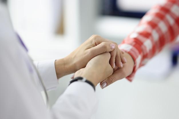 Médico de jaleco branco apertando as mãos de paciente em conceito de tratamento bem-sucedido de closeup clínica