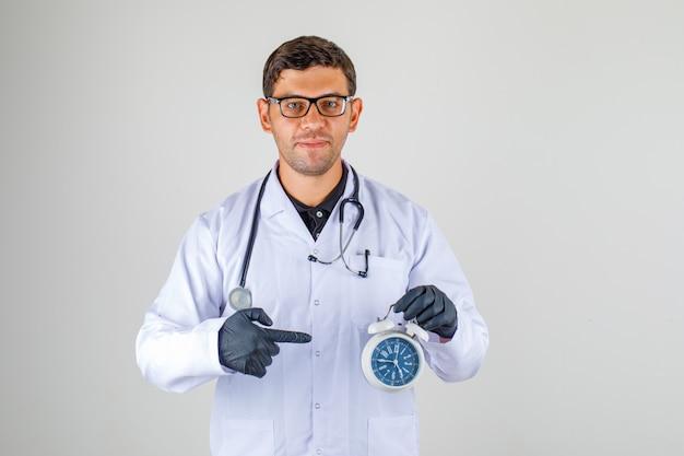 Médico de jaleco branco com estetoscópio segurando o relógio despertador