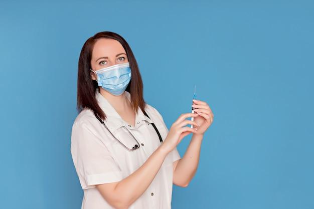 Médico de jaleco branco com um estetoscópio em uma máscara médica detém uma seringa nas mãos