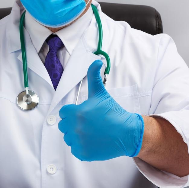 Médico de jaleco branco e gravata mostra com a mão um gesto como, usando luvas médicas de látex azuis