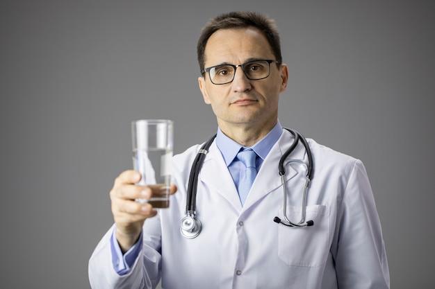 Médico de jaleco branco tem um copo de água nas mãos. sede. nutrição apropriada.
