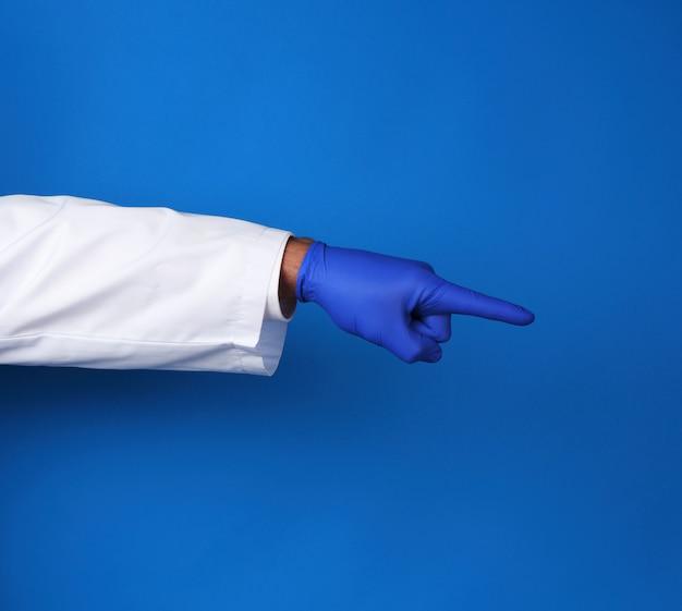 Médico de jaleco branco, usando luvas estéreis azuis, mostrando o gesto com a mão indicando o assunto, fundo azul