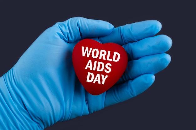 Médico de luvas azuis segura um coração com o texto 01 dia mundial da aids, conceito.