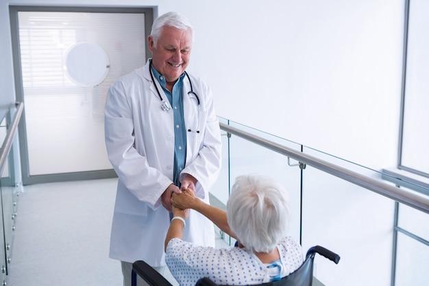 Médico de mãos dadas com paciente sênior