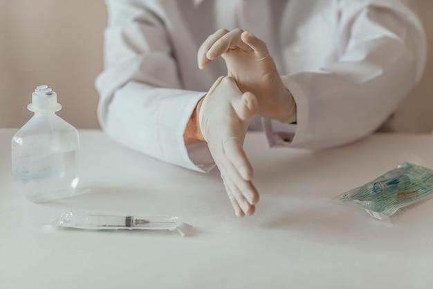 Médico de medicina calçando luvas protetoras antes do exame em uma mesa branca. seringa