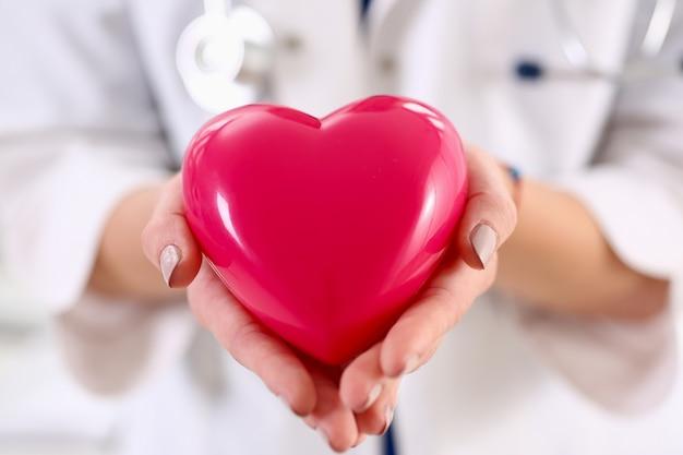 Médico de medicina feminina com as mãos segurando um coração vermelho