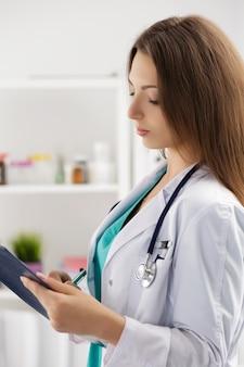Médico de medicina feminina preenchendo a lista de histórico médico do paciente durante a ronda da ala. conceito de assistência médica ou seguro
